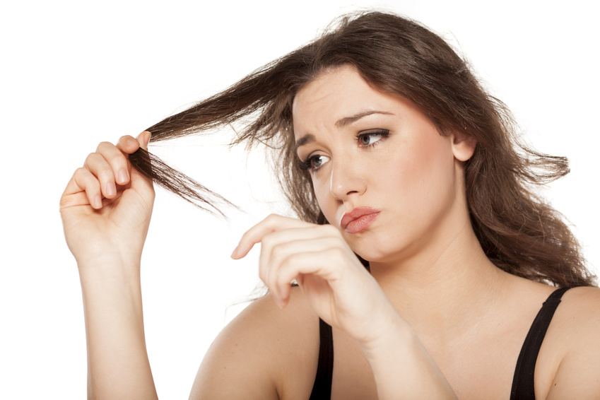 dissapointed young woman looks at the tops of her hair
